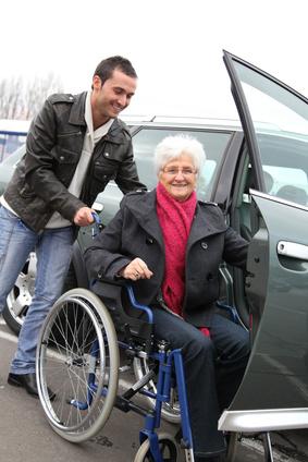 Jeune homme aidant une femme senior en fauteuil à monter en voiture