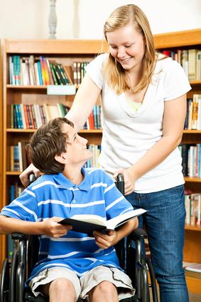 Jeune fille accompagnant un jeune homme en fauteuil