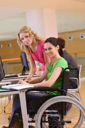 Personne en fauteuil à son poste de travail avec une tablette électronique