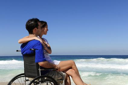 Une femme et son mari en fauteuil à la plage