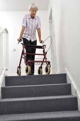 Une femme âgée avec un déambulateur en haut d'un escalier