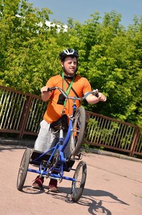 Homme trisomique sur un tricycle