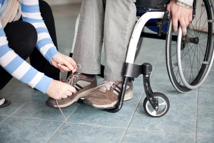 Personne aidant un handicapé à lacer ses chaussures