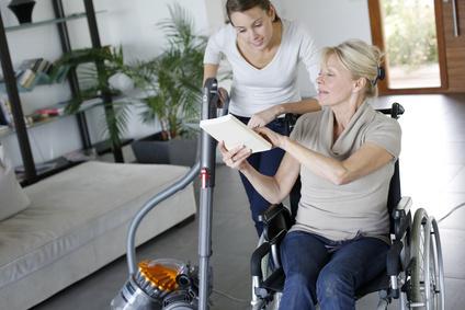 Jeune femme aidant une personne en fauteuil à domicile